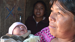 A mother holding her baby with a young girl in the background