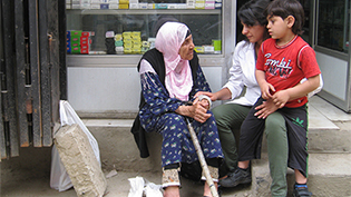 Elderly woman being tended to by a woman doctor who has a child on her knee