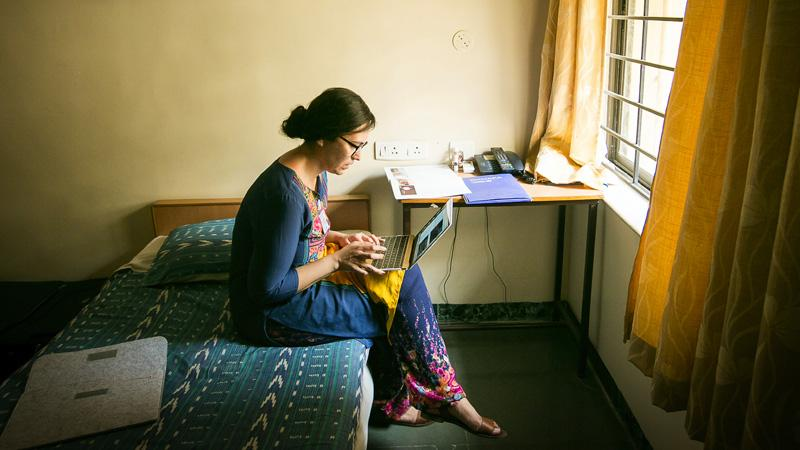 Woman in a foreign country, sitting on a bed, working on her laptop