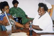 A health worker checks a client's blood pressure in Zambia.