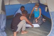UCSF Institute for Global Health Sciences student Hailey Reeves working in a tent with two male nurses from Madagascar